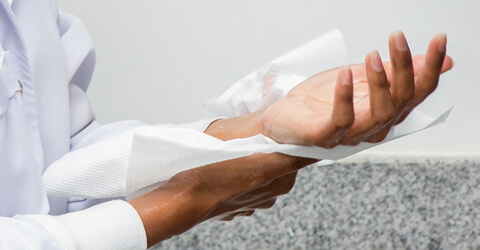Employee drying hands with paper towel after washing hands